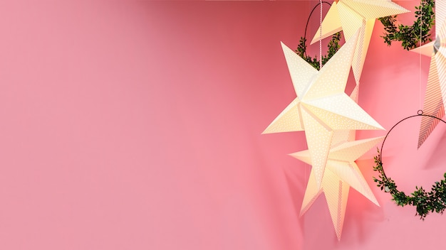 Festive garland in the form of star with light, wreaths, for christmas, new year, holiday on purple, pink background. home decor.