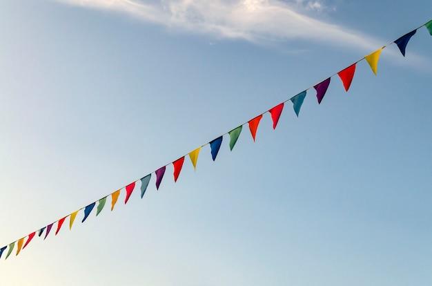Праздничные гирлянды, развевающиеся цветные ленты, фон голубого неба, обложка сайта о радостном настроении, фестивале.