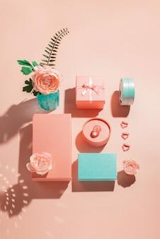 밝은 그림자가있는 파스텔 색상의 선물 상자와 꽃의 축제 기하학적 배열