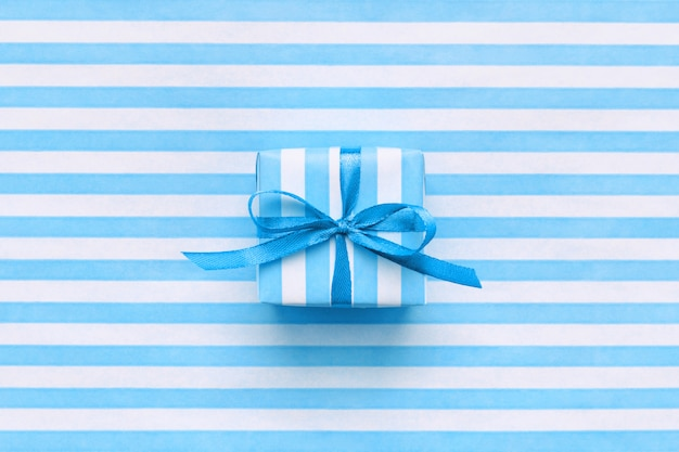 Festive gift box on blue and white striped wrapping paper