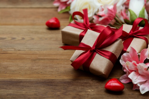 Festive gift boxes and bouquet of flowers on wooden background with copy space. valentine's day, love.