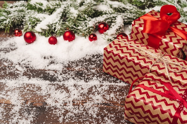 Festive gift with bow close up on wooden background with snow