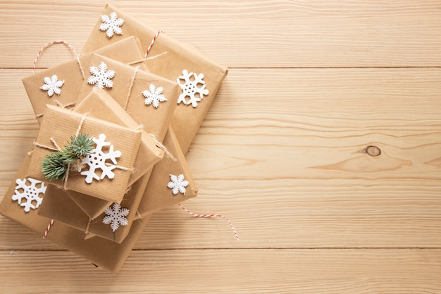 Festive gifts with snowflakes on wooden background