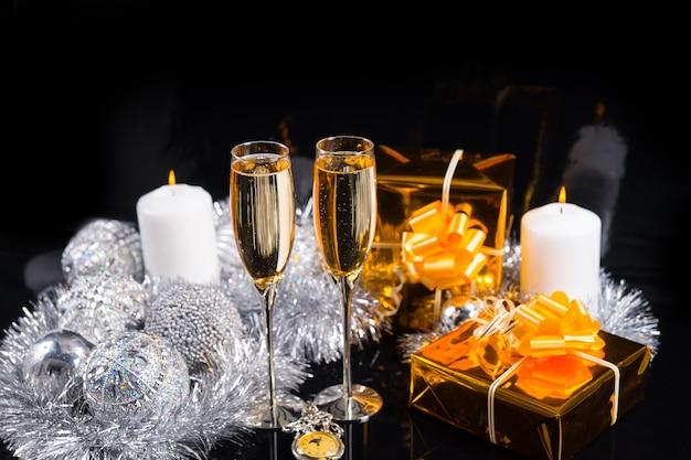 お祝いのきらびやかなクリスマスの静物-懐中時計、シャンパングラス、金の紙に包まれたギフト、炎のキャンドル、黒の背景に銀の装飾