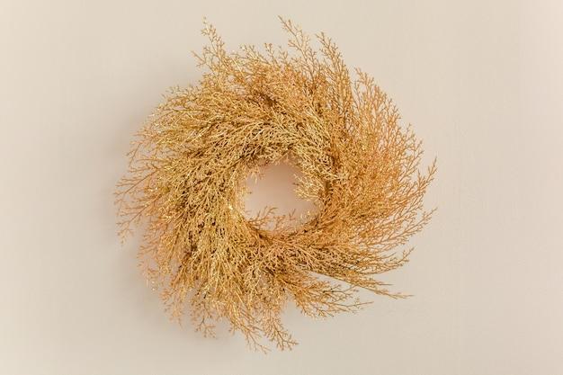 ベージュの壁にお祝いの金の花輪
