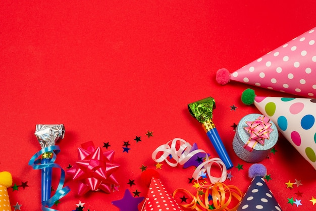 Праздничные золотые и фиолетовые звезды конфетти и подарка, шапки на день рождения на красном фоне. место для текста или дизайна.