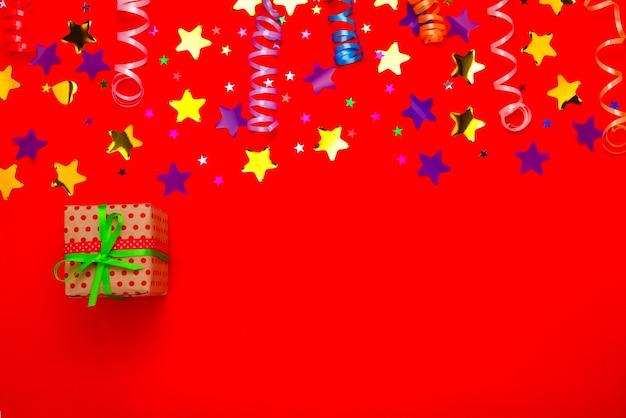 Праздничные золотые и фиолетовые звезды конфетти и подарок на красном фоне. место для текста или дизайна.