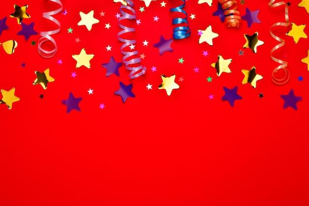 Праздничные золотые и фиолетовые звезды конфетти на красном фоне. место для текста или дизайна.