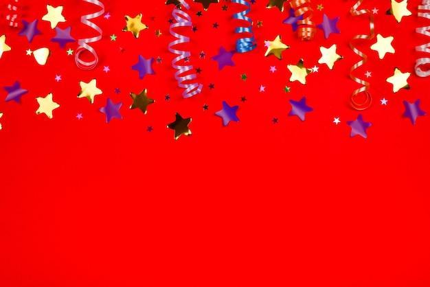 赤い背景に紙吹雪のお祝いの金色と紫の星。テキストやデザインのためのスペース。