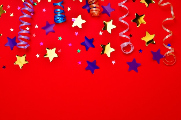 Праздничные золотые и фиолетовые звезды конфетти на красном фоне