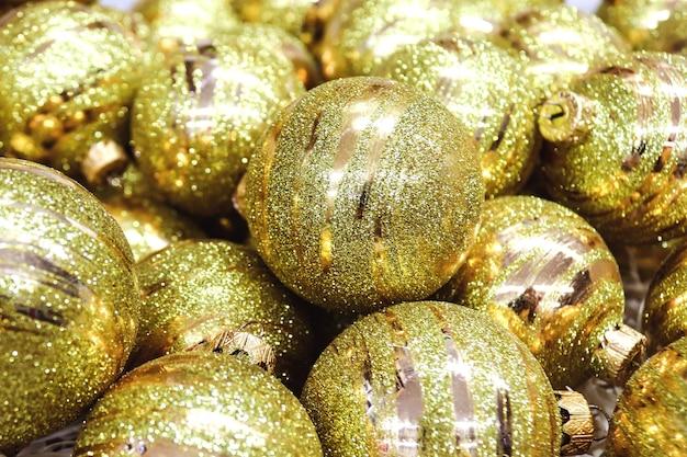 Праздничные золотые елочные шары крупным планом. выборочный фокус. рождество и новый год фон