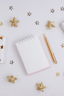 Festive golden decorations and empty notebook on white background. flat lay. planning concept.