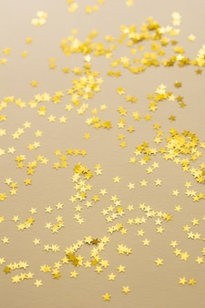 Festive golden stars of confetti are scattered on a light background.