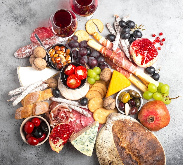 スナックと前菜、チーズ、肉、オリーブ、パン、フルーツ、カナッペ、グラスワインのお祝いのグルメミックス。イタリアの前菜セットまたはスペインのタパスバー。共有する食べ物、パーティーやピクニックの時間、上面図