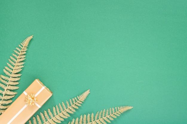 금 장식이 있는 축제 녹색 배경, 반짝이는 황금빛 고사리 잎과 선물 상자가 있는 배경, 평평한 평지, 위쪽 전망, 복사 공간