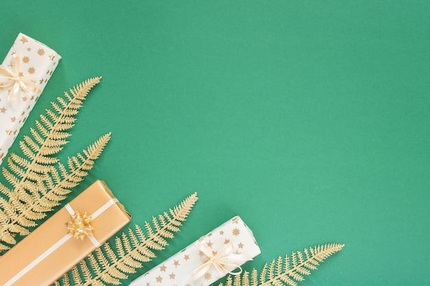 金の装飾が施されたお祝いの緑の背景、キラキラ輝く金色のシダの葉とギフト ボックス、フラット レイアウト、トップ ビュー、コピー スペースの背景