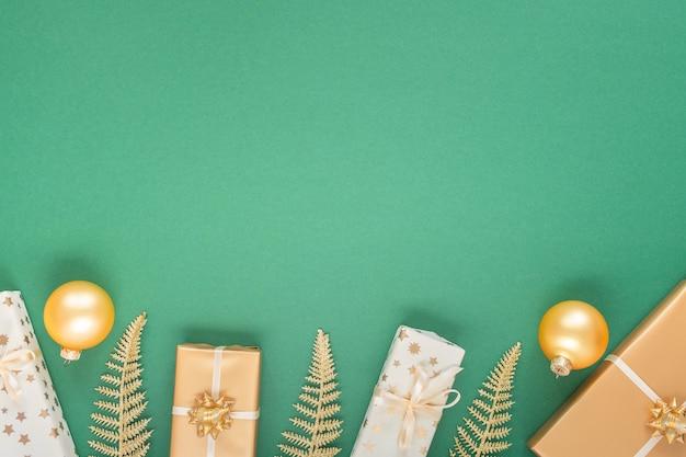 금 장식이 있는 축제 녹색 배경, 반짝이는 황금빛 고사리 잎이 있는 배경, 크리스마스 공이 있는 선물 상자, 평평한 평지, 위쪽 전망, 복사 공간