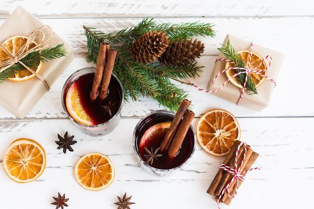 Праздничная открытка с глинтвейном, упакованными подарочными коробками и традиционными специями на белом столе