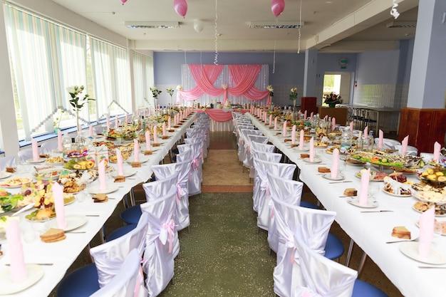Праздничный зал со столом, накрытым для свадебного торжества