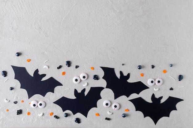 お祝いのハローインの背景。ベージュの背景、テキストのコピー、選択的な焦点に装飾的な目を持つ装飾的な紙コウモリ
