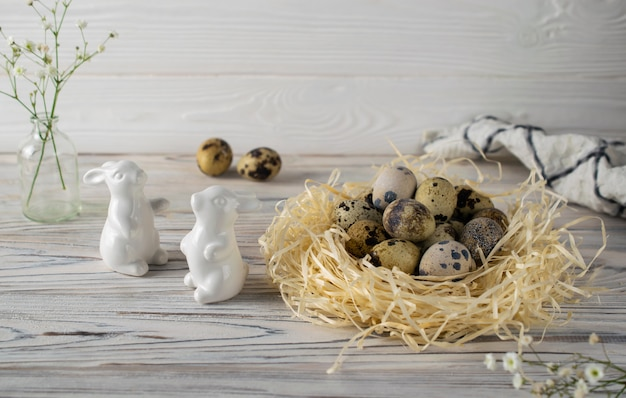 Festive happy easter decoration with quail eggs and ceramic bunnies