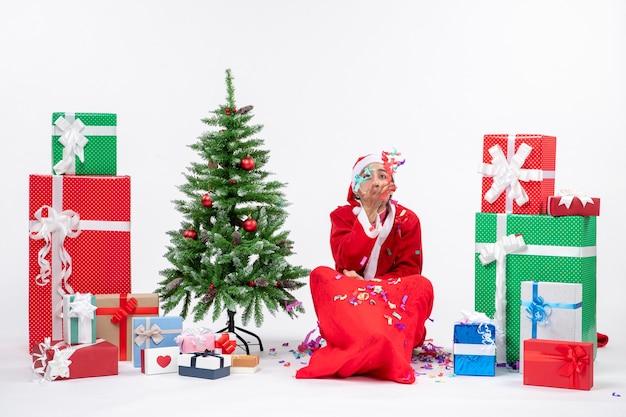 Праздничное праздничное настроение с забавным позитивным санта-клаусом, сидящим на земле и играющим с рождественскими украшениями возле подарков и украшенной рождественской елкой на белом фоне