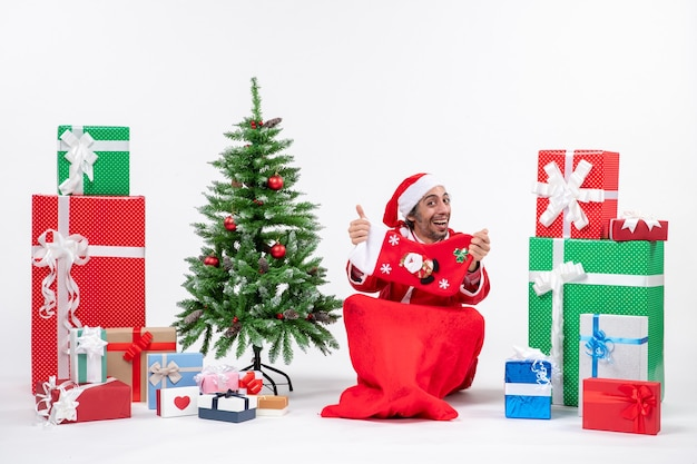 Festive holiday mood with funny positive surprised santa claus sitting on the ground and showing christmas sock near gifts and decorated xsmas tree on white background