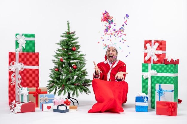 Праздничное праздничное настроение с забавным позитивным удивленным санта-клаусом, сидящим на земле и играющим с рождественскими украшениями возле подарков и украшенной рождественской елкой на белом фоне