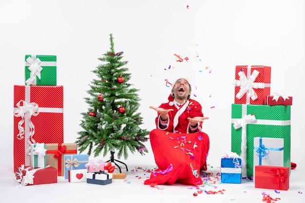 Праздничное праздничное настроение со счастливым санта-клаусом, сидящим на земле и играющим с рождественскими украшениями возле подарков и украшенной рождественской елкой на белом фоне