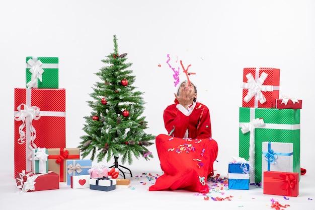 Umore di festa festiva con babbo natale positivo seduto per terra e giocando con decorazioni natalizie vicino a regali e albero di natale decorato su sfondo bianco