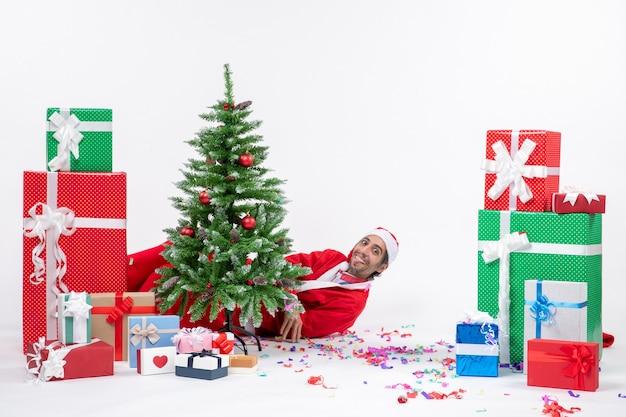 Umore festivo di festa con babbo natale che si trova dietro l'albero di natale vicino a regali su priorità bassa bianca