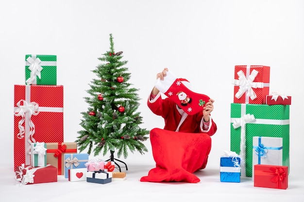Festive holiday mood with santa claus sitting on the ground and closing his face with christmas sock near gifts and decorated xsmas tree on white background