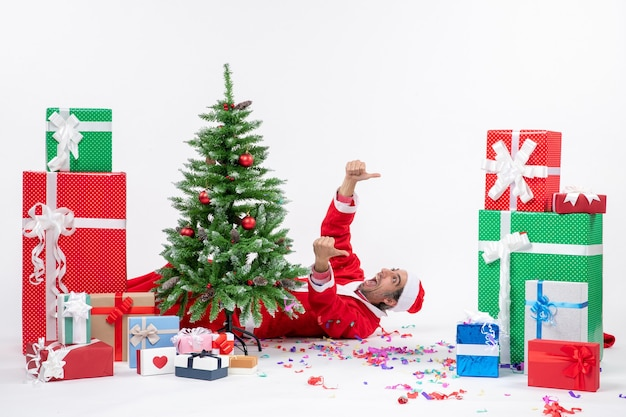 Umore di festa festiva con il giovane babbo natale positivo che si trova dietro l'albero di natale vicino a regali su priorità bassa bianca