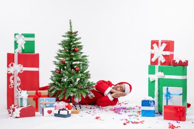 Праздничное праздничное настроение с молодым дедом морозом, лежащим за елкой возле подарков разных цветов на белом фоне stock photo