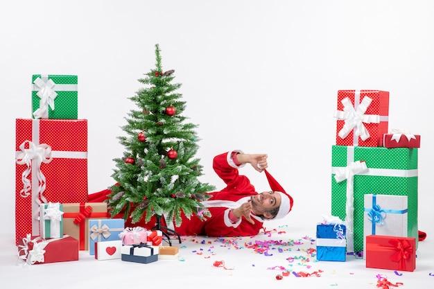 Праздничное праздничное настроение с молодым дедом морозом, лежащим за елкой возле подарков на белом фоне stock photo