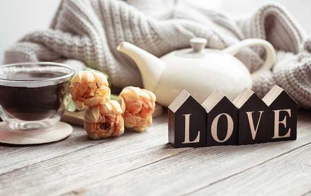 Праздничный домашний натюрморт с цветами, чашкой чая и чайником на деревянной поверхности заделывают.