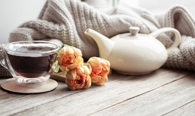 Festosa casa ancora in vita con fiori, una tazza di tè e una teiera su una superficie di legno da vicino.