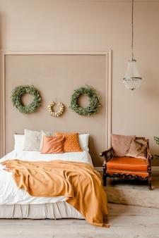 花輪のトウヒの枝の金のおもちゃとスカンジナビアスタイルのお祝いのインテリアベッドルーム