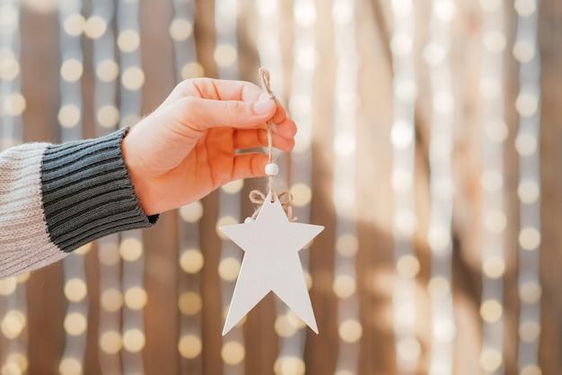 Праздничный декор интерьера. крупный план мужской руки, держащей белый звездный орнамент ручной работы над размытыми сияющими сказочными огнями.