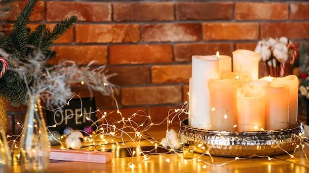 축제 인테리어 장식. 요정 조명, 양 초, 흐림 벽돌 벽 위에 전나무 나뭇 가지의 배열.