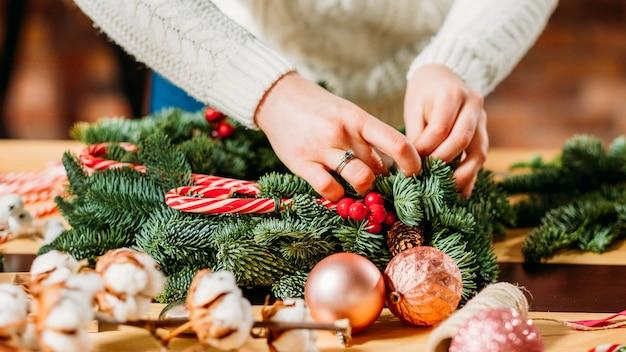 축제 인테리어 디자인. 녹색 전나무 나무 나뭇 가지, 목화 식물을 사용하여 크리스마스 장식을 만드는 전문 플로리스트 손의 근접 촬영.