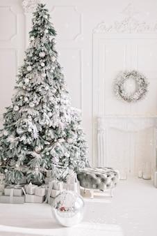Праздничный интерьер. роскошная елка, украшенная огнями, с подарками