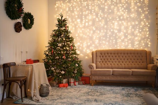 편안한 소파와 장식 된 크리스마스 트리가있는 축제 인테리어
