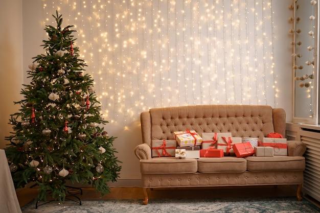 Праздничный интерьер с множеством подарков на удобном диване и украшенной елкой