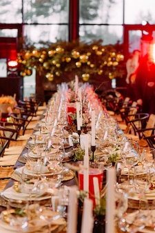 Festive large table decorated with christmas symbols candles sparkle party celebration luxury hall