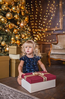 Festive little blonde girl in glitter dress opening a gift at home in the living room with christmas decoration