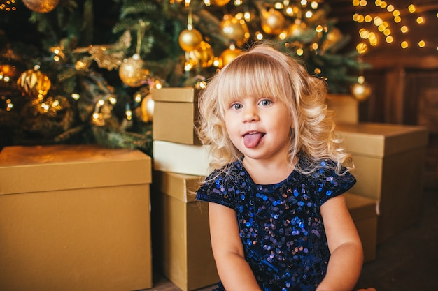 Festive little blonde girl opening a gift at home in the living room with christmas decoration and showing her tongue