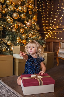 Festive little blonde girl opening a gift at home in the living room with christmas decoration and showing somewhere with her finger