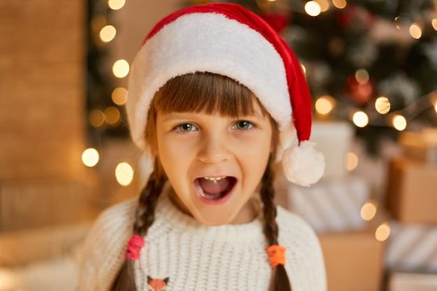 Праздничная маленькая рождественская девочка в шляпе санта-клауса с двумя косичками
