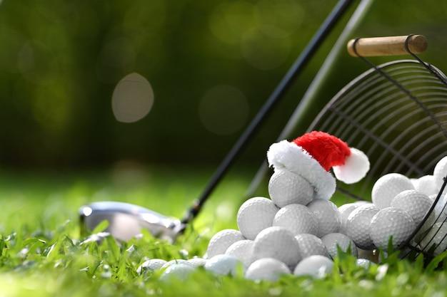 골프 코스 배경에 휴가 시즌 동안 위에 산타 클로스의 모자와 함께 티에 축제처럼 보이는 골프 공